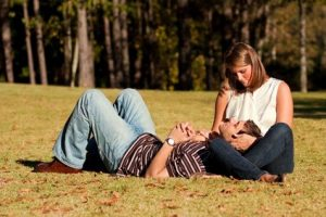A young couple in love share an intimate moment while laying on a grassy field.